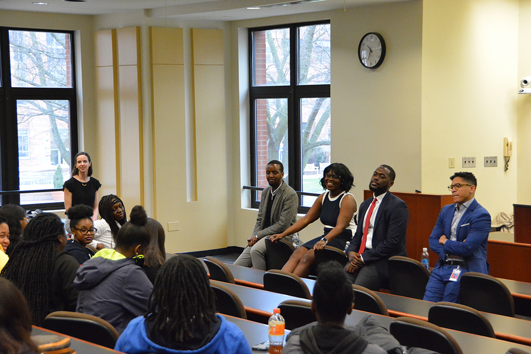 A panel of legal professional sit at the front of a room, speaking to a group of high school students.