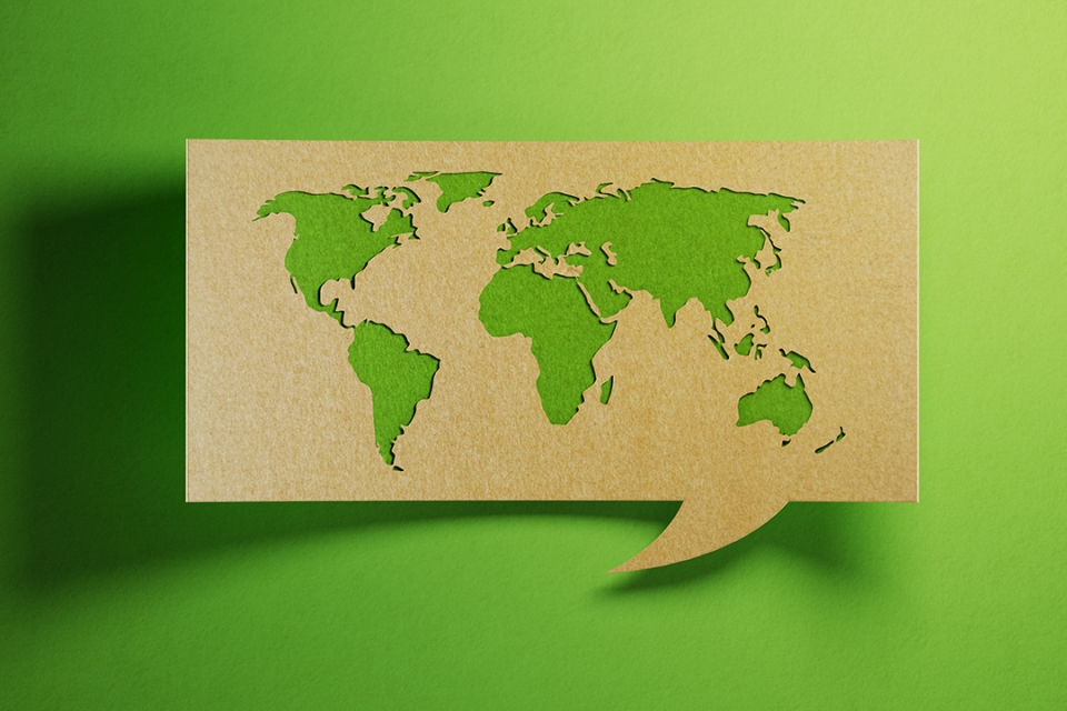 Map of the earth made out of cardboard on a green background