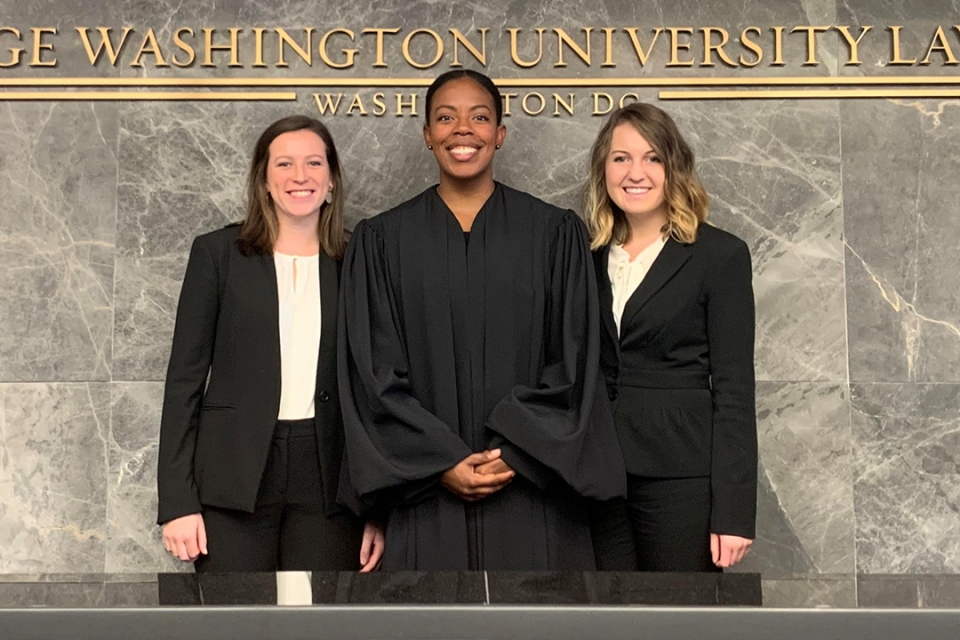 Two students stand beside a judge, who ruled they won a mock trial competition.