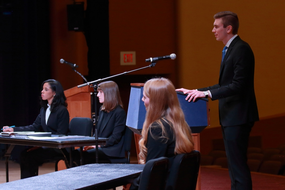 Shane Roberts, 2L, stands behind a podium presenting his argument at the 2020 Van Vleck Constitutional Law Moot Court Finals.