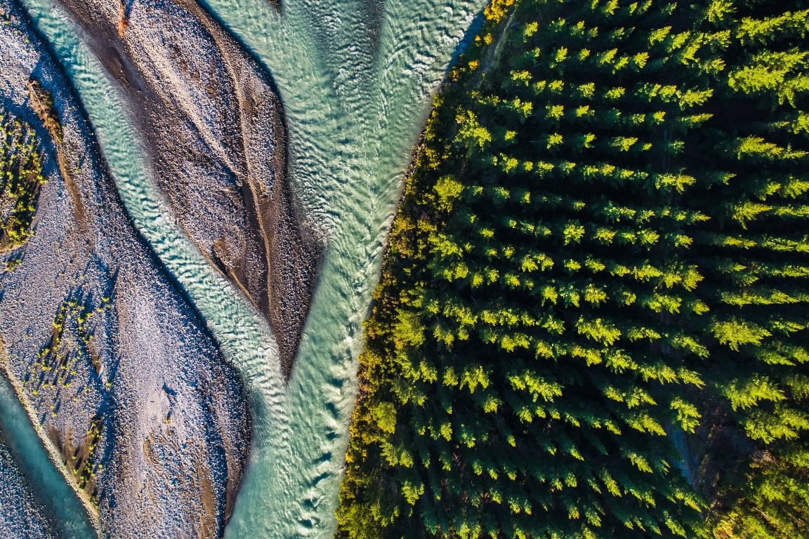 Overhead photograph of a river next to a forest.