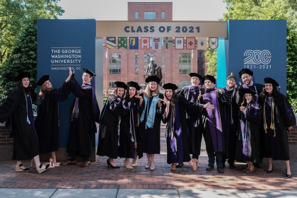 Graduates in regalia standing under arch that says Class of 2021