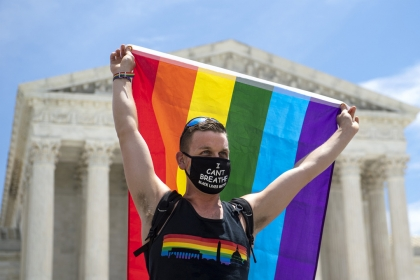 Joseph Fons hold up Pride Flag in front of Supreme Court of United States