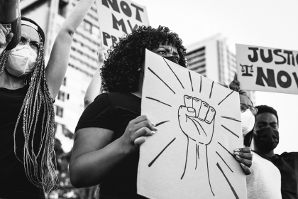 Woman holding sign with fist