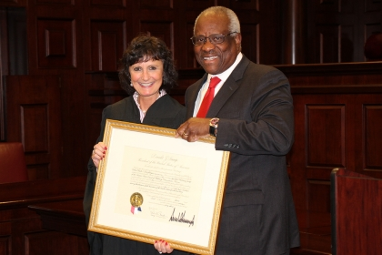 Associate Dean Lisa Schenck stands with Supreme Court Justice Clarence Thomas, holding Dean Schenck's award for being appointed.