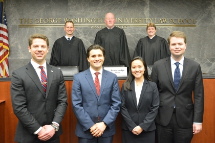 Three JAG judges stand behind the bench, with four GW Law students standing in front for a group photo.