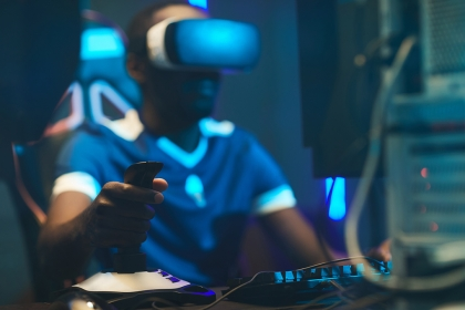 Person playing an esports game with alternate reality glasses in front of a computer.