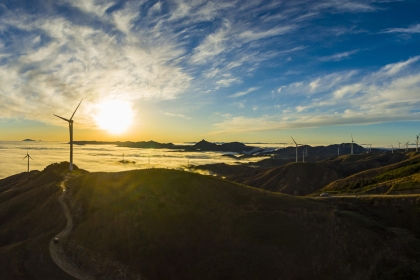 Image of a sunrise overlooking a valley of wind turbines