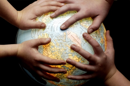 Photo of hands on a globe
