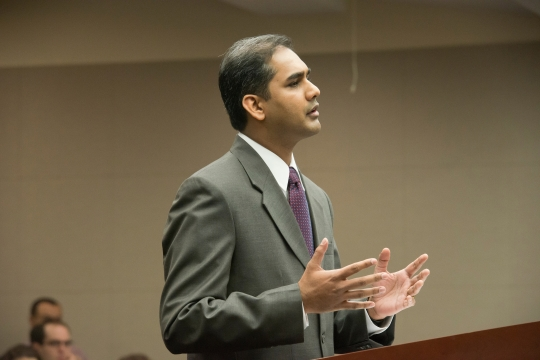 Student in a suit speaks at a podium
