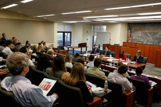 A crowd of people sit, listening to four legal experts discuss cases in the front of a room.